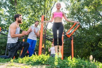 Low-angle view of a beautiful young woman jumping rope in the applauses of her friends, during cardio workout routine in a modern outdoor fitness park