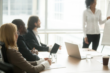Diverse business people executive team listening to presentation, multiracial businesspeople sitting at conference meeting table at briefing, attending corporate group training or business seminar