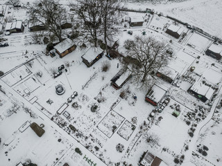Aerial view of allotment covered in snow with tiny houses