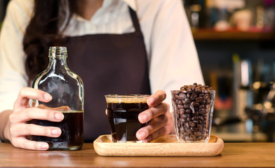 Girl barista bartender waiter in uniform making coffee, Girl barista bartender waiter in uniform making coffee,Asian Barista woman Cold brew coffee in glass bottle to a cup glass in the coffee shop. p