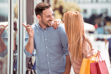 Young couple pointing at window shopping.