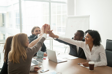 Excited african and caucasian business team giving high five at office meeting motivated by victory, achievement or good work result, multi-ethnic employees group celebrate corporate success together