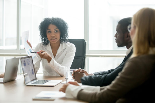 African businesswoman showing good statistics report explaining deal advantages convincing multiracial partners at negotiations meeting, black manager consulting diverse clients promising benefits