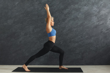 Woman training yoga in hero pose in gym