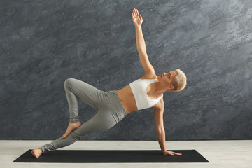 Woman training yoga in side plank pose
