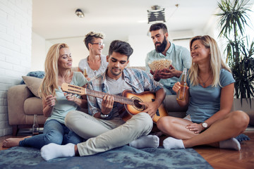 Happy young friends playing guitar