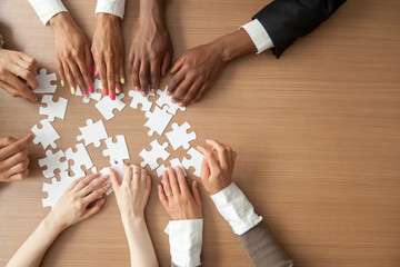 Hands of multi-ethnic team assembling jigsaw puzzle, multiracial group of black and white people joining pieces at desk, successful teamwork concept, help and support in business, close up top view
