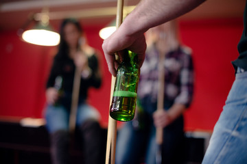 Man is holding beer and billiard stick