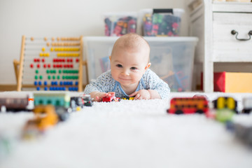 Cute little baby boy, playing with toy cars on the carpet in children room