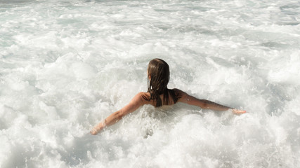 girl is having fun on waves, foam of waves