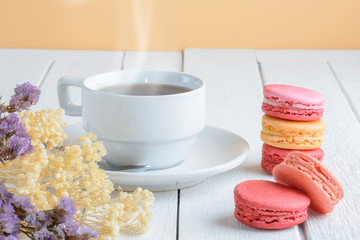 Different types color of macaroons with Cup of hot tea on white wooden background