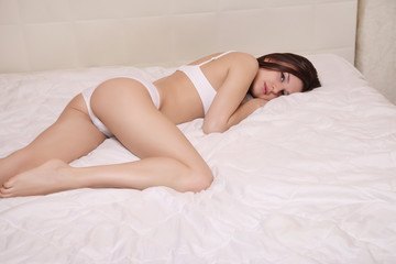 beautiful girl lying on a white bed