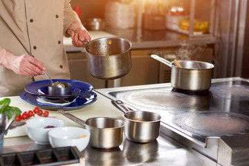 Male chef putting dish in plate. Chef at professional kitchen putting stewing vegetables in steel ring. The process of finishing a dish by chef in restaurant.