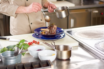 Chef pouring with sause lamb shank. Male chef hands at professional european kitchen pouring lamb shanks with sauce. Tasty and nutrition dish.