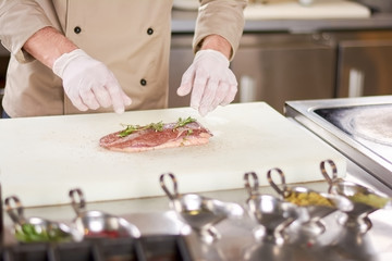 Duck raw breast with rosemary. Raw fillet of duck breast served with rosemary and ground pepper. Chef cooking meat at work.