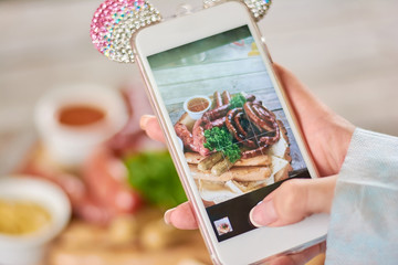 Female hand taking a photo of grilled sausages. Young woman hand using smartphone to take a photo of appetizing grilled sausages.
