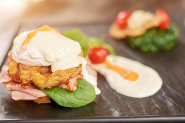 Appetizing benedict with ham. Fresh cooked benedict in restaurant. Delicious dinner on table.