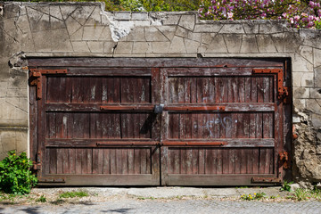 Old brown wooden gate with lock in a stone fence