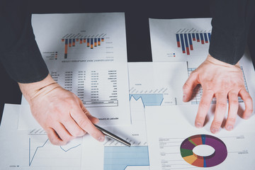 Analyst is working on reports and graphs. The man analyzes the graphs of reports, checks costs and revenues. Financial growth, market research. The development of companies and corporations.