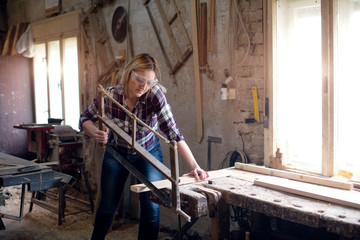 Carpenter woman is cutting wood