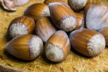 Tasty hazelnuts on a wooden kitchen table. Forest specialties and kitchen accessories.