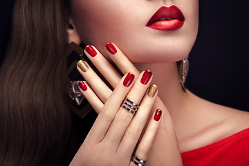 Beautiful woman with perfect make-up and red and golden manicure wearing jewellery