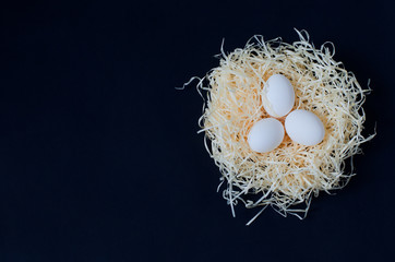 Three white eggs in a nest on a dark background. Image with free space for text. Picture for the celebration of Easter