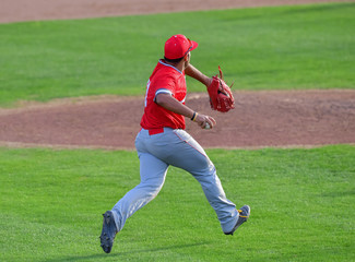 Baseball Third baseman fielding the ball and making a strong throw to first base