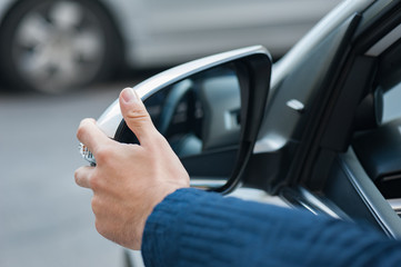 Young human hand is preparing or correct car mirror for the trip or travel from car window.