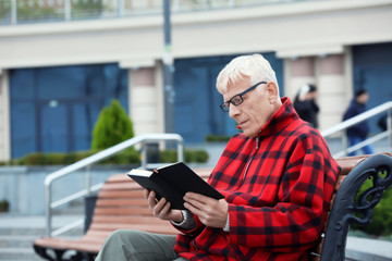 Handsome mature man reading book on bench outdoors