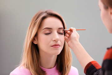 Makeup artist working with beautiful model indoors