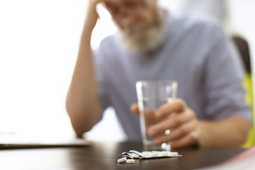 Senior man with pills and glass of water at workplace