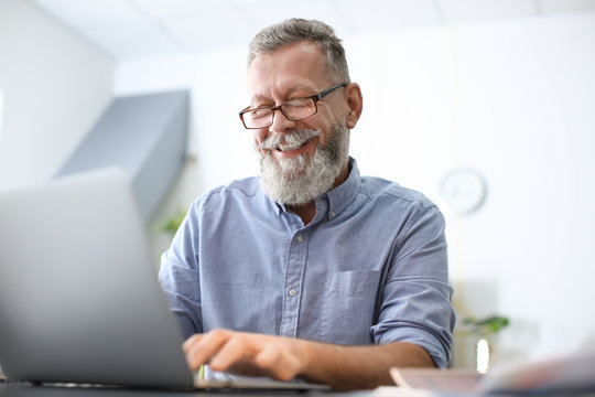 Senior man working with laptop at table in office
