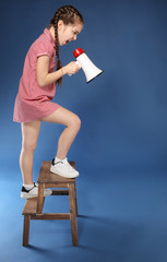 Emotional little girl shouting into megaphone while standing on stool against color background