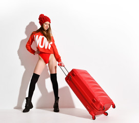 Young sexy woman in fashion red body cloth and hat with traveler luggage bag on white