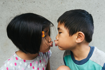Asian American toddlers getting ready to kiss each other with puckered lips