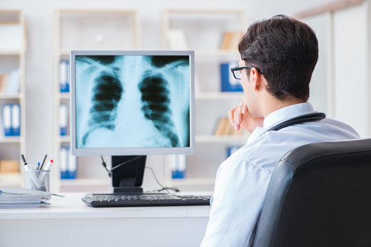 Rear view of doctor looking at x-ray on computer