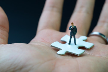 Business success strategy with missing jigsaw key person, miniature people businessman thinking and standing on  white jigsaw puzzle piece in real human hand, dark black background.
