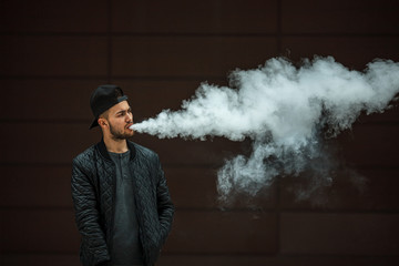 Vape man. Portrait of a handsome young white guy in a modern black cap vaping and letting off puffs of steam from an electronic cigarette opposite the