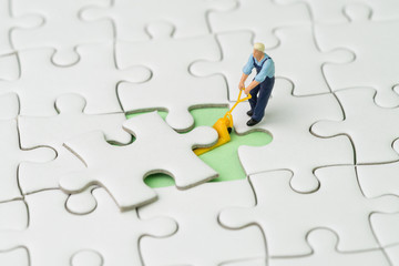 Fulfill the missing piece for business success strategy concept, miniature worker figurine using the forklift to complete the missing white jigsaw puzzle piece on pastel green background