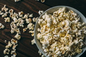 Popcorn in plate on wooden table, top view