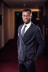 african business man with glasses in jacket and tie looks away