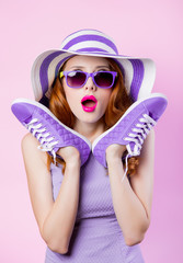 girl in sunglasses and hat holding shoes