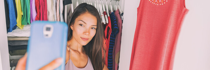 Selfie Asian girl taking photo with phone at home bedroom. Clothes outfit in walk-in closet. Shopping girl using smartphone fashion app posting on social media. Banner panorama.