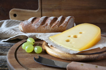 Maasdam cheese, french bread and green grapes  on wooden table