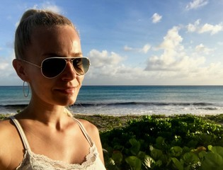 Beautiful blonde female model with sunglasses in Oistins, Barbados at a untouched beach with lush greenery, crystal clear turquoise water and a blue sky with white clouds