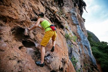 female rock climber climbing on steep cliff
