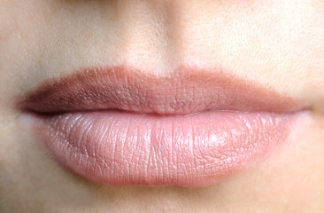 Women's lips with a nude lipstick, view front