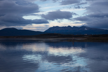 Sunset in Ushuaia with dark gray and blue clouds. A reflection of the sunset is seen in the water.