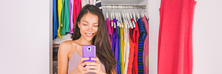 Selfie Asian girl taking photo with phone of outfit in walk-in closet dressing room. Clothes fashion stylist. Shopping girl using smartphone fashion app posting on social media. Banner panorama.